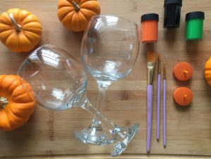 Two clean and dry wine glasses. Paint brushes in a variety of sizes. Acrylic paint white, black, green, and orange. Tea light candles to sit on top of green stem (optional).